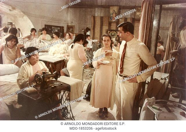 Italian actor and director Giancarlo Giannini looking at Italian actress Elena Fiore sitting at the typewriter in a scene from the film Seven Beauties