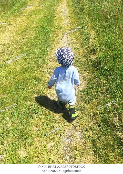 A toddler has a spring in his step as he walks on a grassy path, Halifax, Nova Scotia, Canada