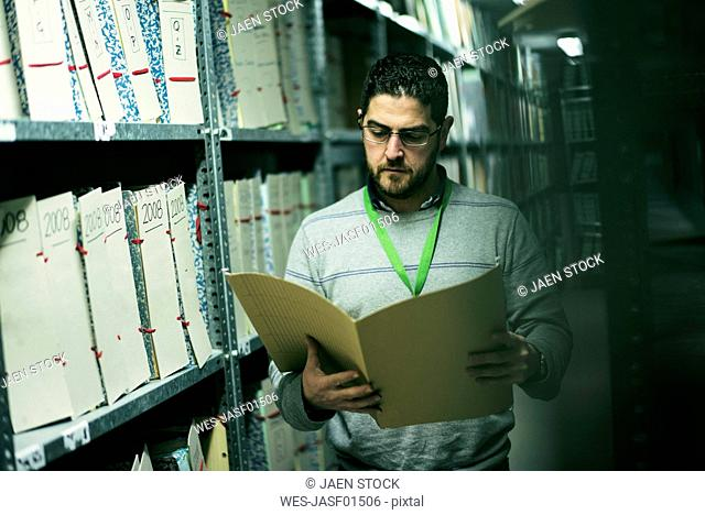 Portrait of serious man reading documents in an archive