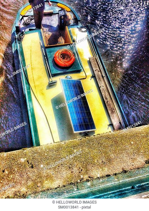 Barge with solar panel being steered under bridge, England