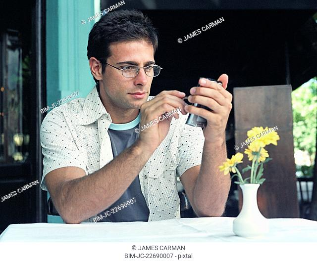Hispanic man using electronic organizer at outdoor cafe