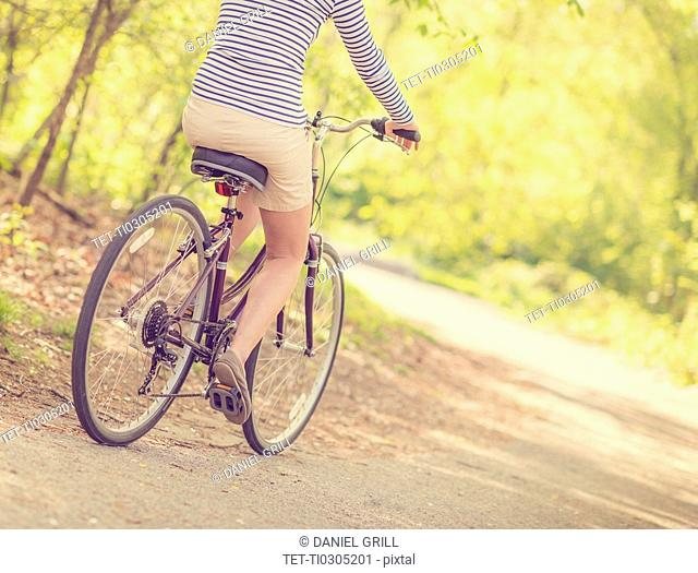 Mid adult woman riding bicycle, low section