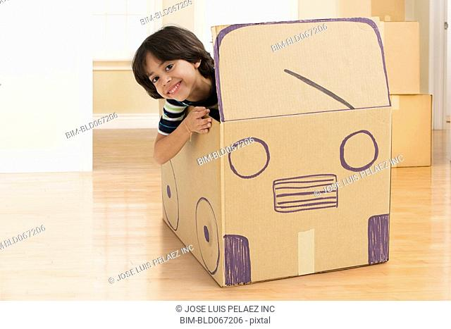 Hispanic boy driving cardboard bus