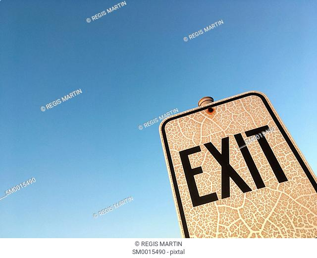 Old and crackled Exit sign against a clear blue sky