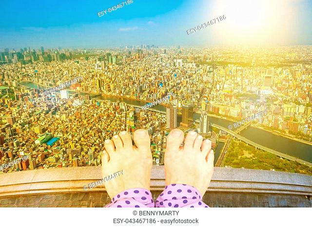 Barefoot girl on top of a building thinking of suicide, over Tokyo cityscape with Sumida River Bridges at sunset. View from high Japan skyscraper
