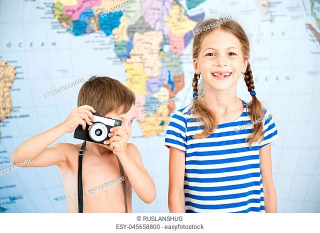funny boy with retro camera and smiling little girl in striped shirt near world map