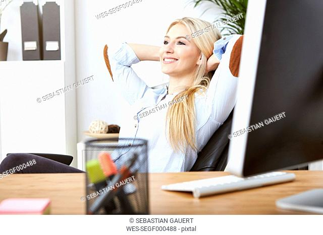 Portrait of smiling blond woman relaxing with hands behind her head at desk in the office