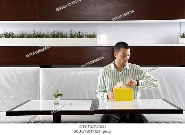 Man with present checking the time in restaurant