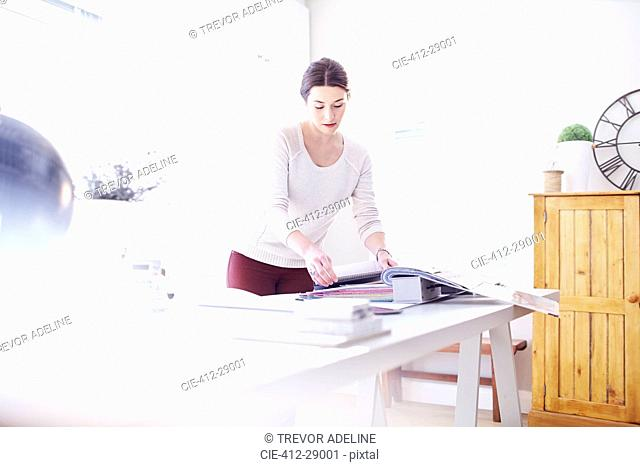 Interior designer browsing fabric swatches in office