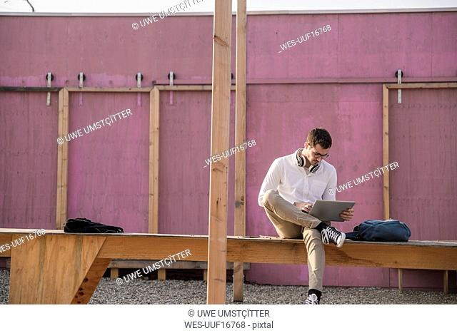 Young man sitting on platform using tablet