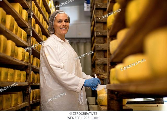 Cheese factory worker applying wax on cheese