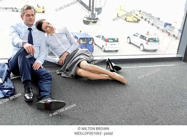 Businessman and businesswoman sleeping at the airport