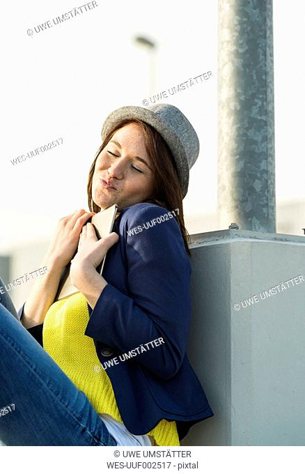 Young woman hugging digital tablet