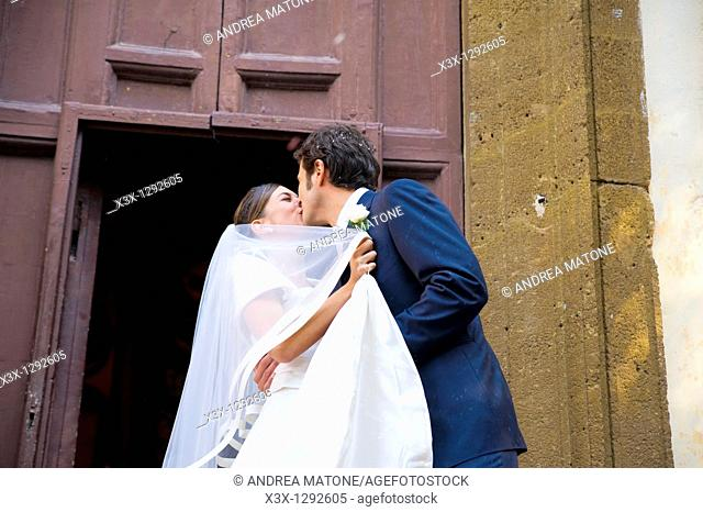 Newlyweds kissing outside church after wedding ceremony