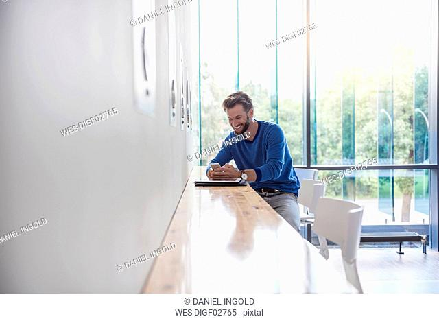 Smiling man looking at cell phone on table by the window