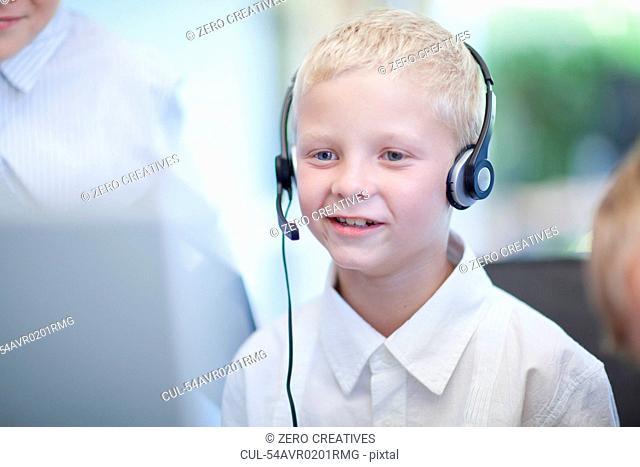 Boy playing businessman at desk