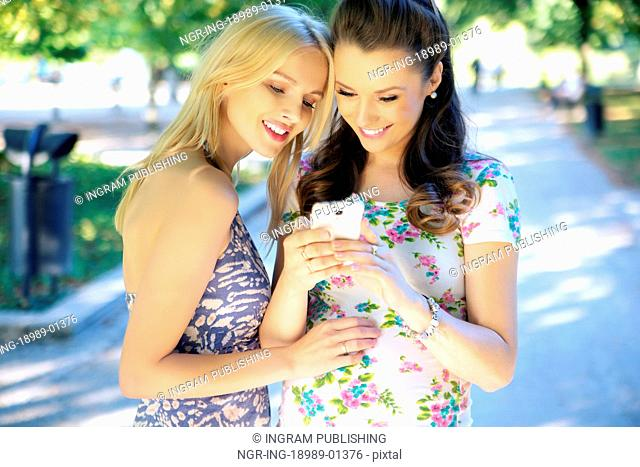 Two young women texting their girlfriend