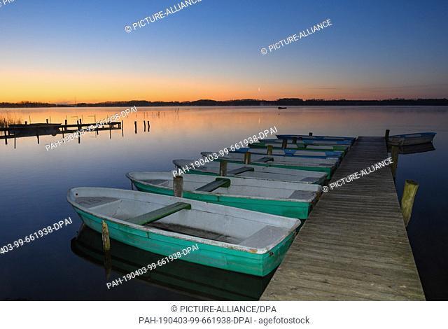 01 April 2019, Brandenburg, Groß Schauen: Köllnitz fishing rowboats lie on a jetty in the light of the morning sun in the Groß Schauener Seenkette nature...