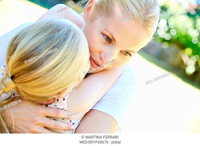 Daughter and mother hugging outdoors