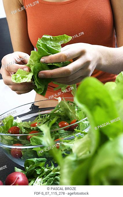 Mid section view of a woman preparing salad