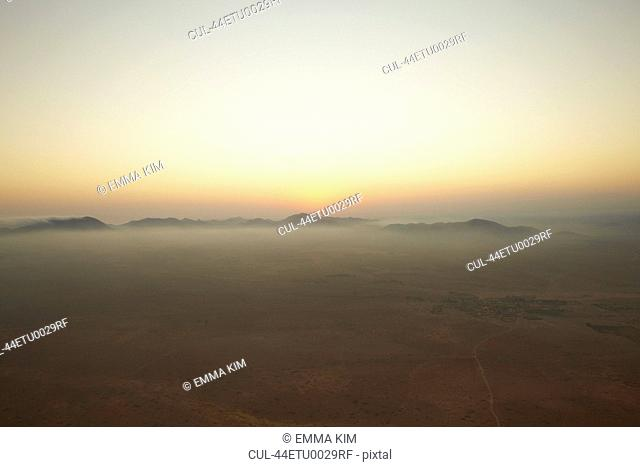 Sun setting over foggy landscape