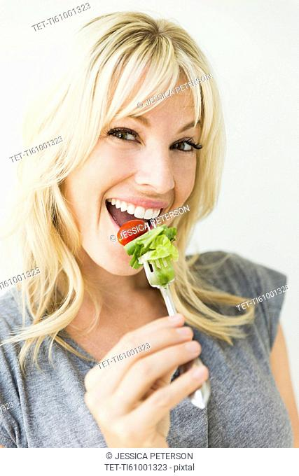 Woman holding salad on fork