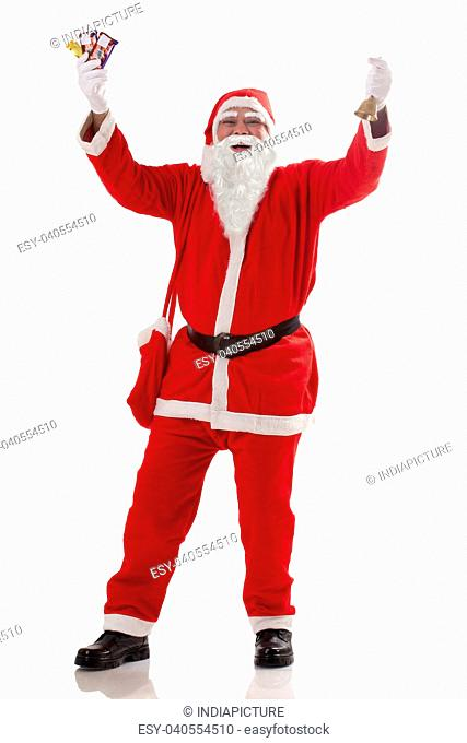 Full length of cheerful Santa Claus with chocolates over white background