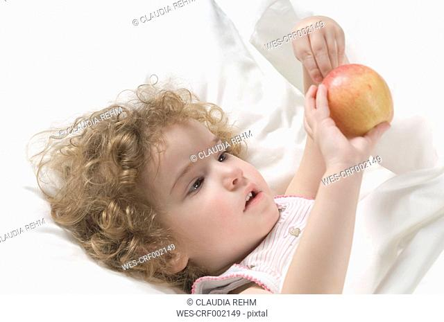 Girl lying on bed with apple