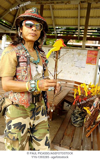 guy selling red and yellow peace doves made from wood , strange people, street life , bangkok, Thailand