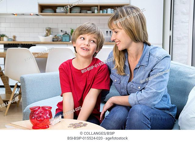 A child counting his pocket money with his mother