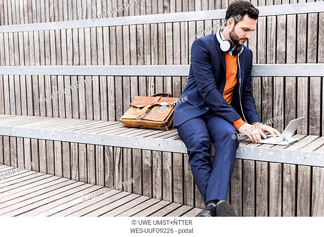 USA, New York City, Businessman sitting on stairs using digital tablet