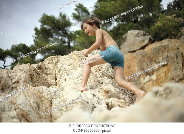 Young boy outdoors climbing on rocks