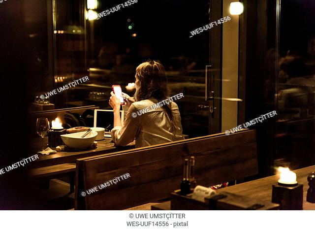 Woman using cell phone at dining table