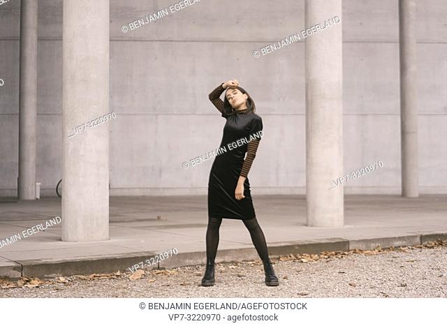emotional woman with closed eyes dancing in front of pillar building in city, Munich, Germany
