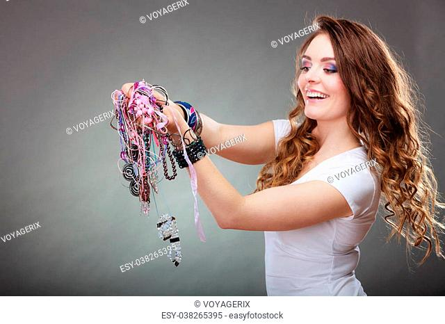 Pretty young woman wearing bracelets and rings holding many plentiful of precious jewelry necklaces beads. Portrait of gorgeous fashion girl in studio on gray