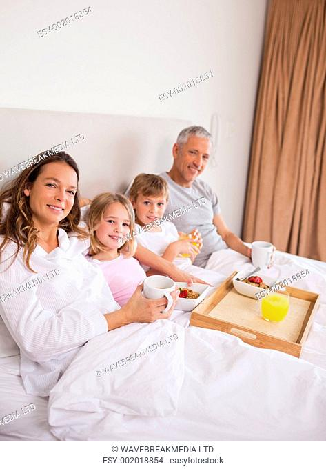 Portrait of a family having breakfast in a bedroom while looking at the camera