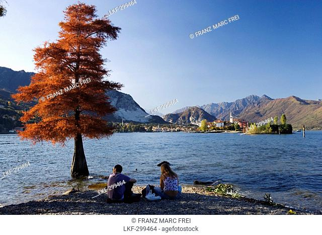 Couple on the lake shore, View from Isola Bella towards Isola Superiore o dei Pescatori, Lago Maggiore, Piedmont, Italy