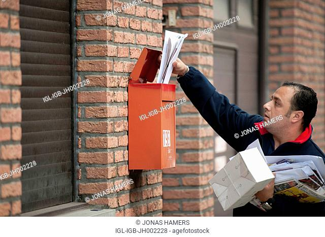 Picture shows belgian postman as he delivers a certified mail / letters / packages during his daily round circuit in the streets