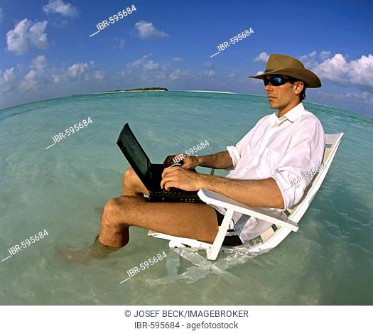 Young man with laptop sitting on deck chair, work and relaxation, vacation and stress, Maldives, Indian Ocean