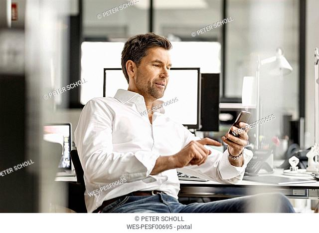 Businessman at desk in office using cell phone