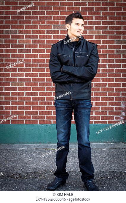 Young man standing near brick wall
