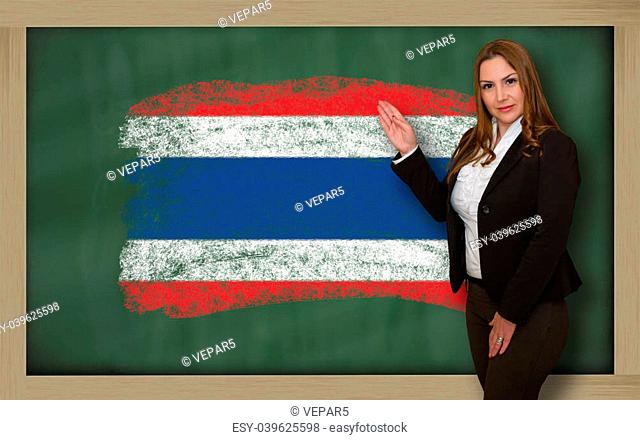 Successful, beautiful and confident woman showing flag of thailand on blackboard for marketing research, presentation and tourist advertising