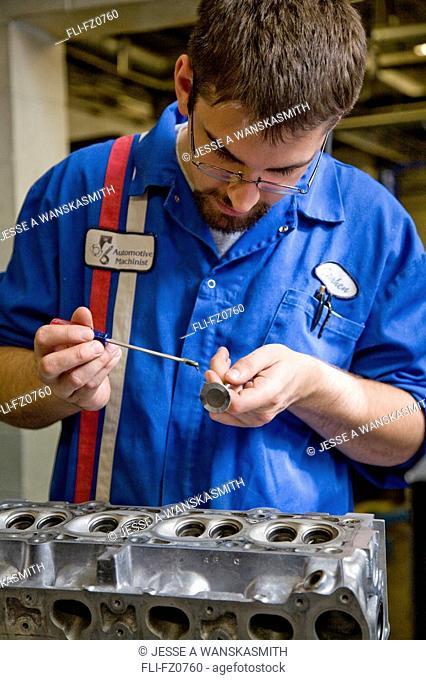 Automotive mechanic adds grease to piston on engine block in machine shop, Spokane, Washington