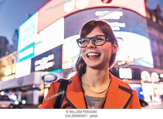 Young woman standing in front of illuminated billboards, smiling