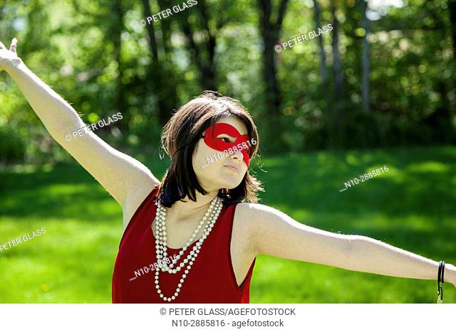 Young woman, with arms outstretched, wearing a mask, pearl necklace, and red dress in a park