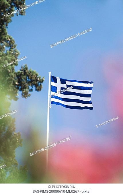 Greek flag fluttering against the blue sky, Athens, Greece