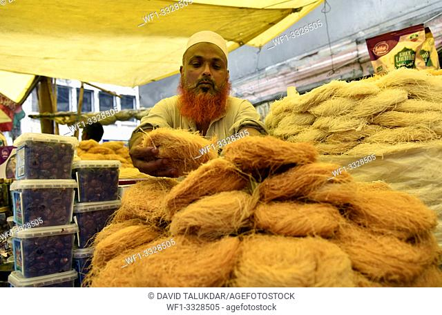 Guwahati, Assam, India. May 21, 2019. Muslim vendor selling vermicelli and other dry fruits at a market stall as Ramadan