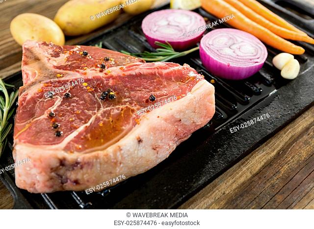 Sirloin chop and ingredients in black box against wooden background