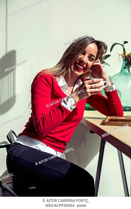 Portrait of laughing woman sitting in a coffee shop drinking cup of coffee
