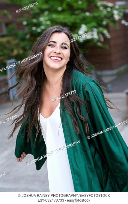 Female college student in a natural light lifestyle portrait while wearing her graduation gown right before graduating from a university